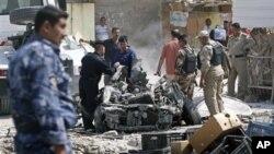 伊拉克安全部隊星期天在巴士拉的汽車炸彈襲擊現場進行檢查