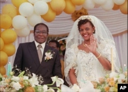 Grace Marufu, the new bride of Zimbabwean President Robert Mugabe, right, waves at guests Saturday, Aug. 17, 1996, after their wedding ceremony at the Kutama catholic mission 42 miles, (80kms )west of Harare.