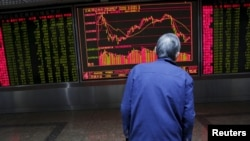An investor watches an electronic board showing stock information on the first trading day after the week-long Lunar New Year holiday at a brokerage house in Beijing, China, Feb. 15, 2016.