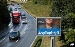 "FILE - A revolving election campaign poster of Germany's anti-immigration party, Alternative fuer Deutschland, AfD, reads ""Asylum fraud"" as Angela Merkel, German chancellor and leader of the Christian Democratic Union party, CDU, appears partially obscured on a billboard in Duesseldorf, Germany, Sept. 14, 2017."