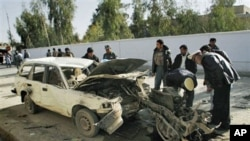 Afghan traffic officers check the engine which is all that remained of the vehicle used in a car bomb explosion, beside a damaged vehicle, after an explosion in Kandahar, south of Kabul, 11 Dec 2010