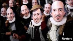 Warga mengenang topeng bergambar foto William Shakespeare pada peringatan 400 tahun kematiannya jalan-jalan Stratford-Upon-Avon, kota kelahirannya di Inggris, Sabtu (23/4).