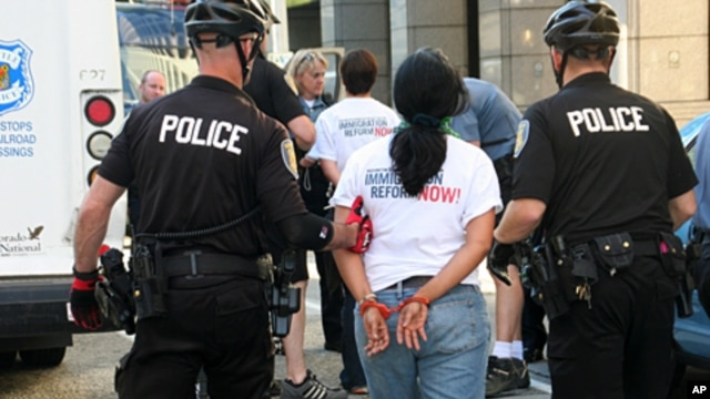 Seattle Police arrest a protester for obstructing traffic during a rally to demand comprehensive immigration reform, 23 June 2010