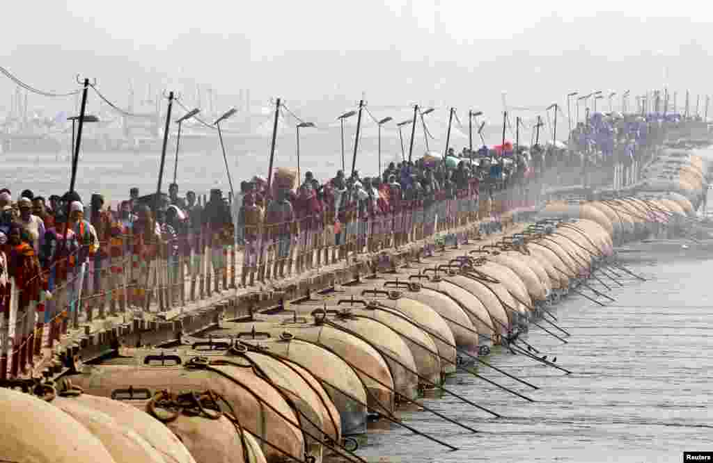 Devotees cross a pontoon bridge after taking a holy dip at Sangam, the confluence of the Ganges, Yamuna and Saraswati rivers, during Magh Mela festival in Allahabad, India.