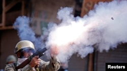 An Indian policeman fires a teargas shell towards demonstrators during a protest against the recent killings in Kashmir, in Srinagar, Sept. 13, 2016.