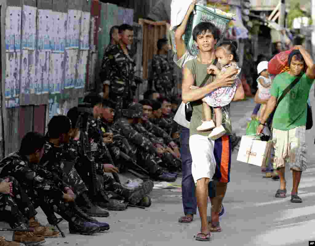 Residents who abandoned their homes carry their belongings during a standoff in Zamboanga, Philippines, Sept. 10, 2013.