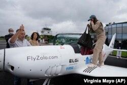Remaja Belgia-Inggris Zara Rutherford, kanan, bersiap untuk masuk ke pesawat Shark Ultralight-nya saat ayahnya Sam Rutherford mengacungkan jempol dan ibunya Beatrice de Smet, tengah, melihat sebelum lepas landas di lapangan terbang Kortrijk-Wevelgem di We