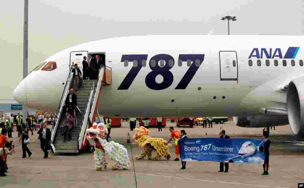 Passengers of a Boeing 787 are welcomed by lion dance to celebrate the airplane's inaugural commercial flight from Japan, at Hong Kong International Airport, October 26, 2011.