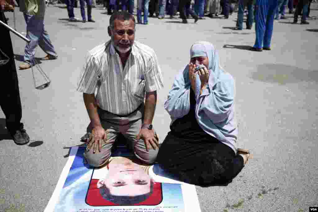 A couple honors one the protesters killed during the uprising, June 2, 2012. (VOA/Y. Weeks)
