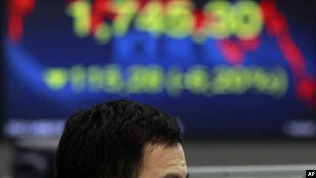 A currency trader reacts as he looks at the monitors at the foreign exchange dealing room of the Korea Exchange Bank headquarters in Seoul, South Korea, August 19, 2011
