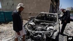 Para pria memperhatikan sebuah mobil yang hancur akibat serangan udara yang dipimpin oleh Arab Saudi di ibukota Yaman, Sana'a, Sabtu, 25 April 2015. (AP Photo/Hani Mohammed)