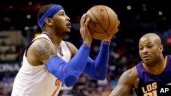 Carmelo Anthony de New York Knicks tire un panier contre Phoenix devant Suns de l' P.J. Tucker qui défend la première moitié du cours d'un match de basket NBA , le mercredi 9 Mars , 2016, à Phoenix . (AP Photo / Matt York )