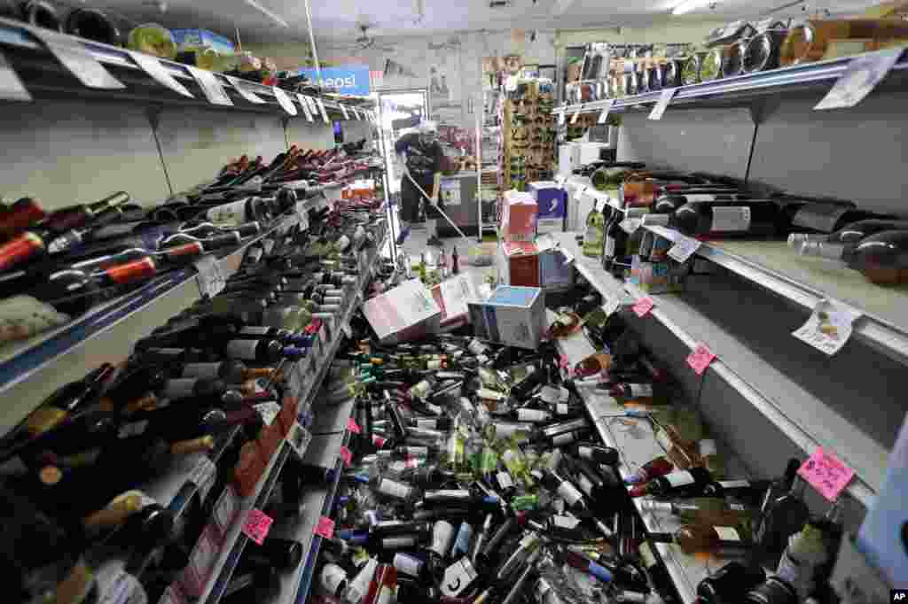Bottles of wine are strewn in the middle of an aisle as Victor Abdullatif, background center, mops inside of the Eastridge Market, his family's store, July 6, 2019, in Ridgecrest, California. Crews in Southern California assessed damage to cracked and burned buildings, broken roads, leaking water and gas lines and other infrastructure after the largest earthquake the region has seen in nearly 20 years jolted an area from Sacramento to Las Vegas to Mexico.