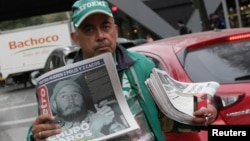 Seorang pedagang kaki lima menjual salinan surat kabar Metro, harian terkemuka Meksiko yang menampilkan gambar Fidel setelah pengumuman kematian pemimpin revolusioner Kuba Fidel Castro, di Mexico City, Meksiko (26/11).