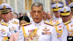 FILE - Thai King Maha Vajiralongkorn, center, holds a candle light during a ceremony at Emerald Buddha temple, in Bangkok, Thailand, May 29, 2018.