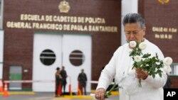 Une femme déposant des fleurs devant l'Académie de police Général Francisco de Paula Santander, au lendemain de l'attentat de l'ELN ayant fait 22 morts à Bogota, Colombie, 18 janvier 2019. (Photo AP/John Wilson Vizcaino)