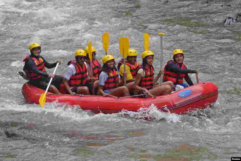 Former United States President Barack Obama (2nd L), his wife Michelle (3rd L) along with his daughters Sasha (C) and Malia (2nd R) go rafting while on holiday in Bongkasa Village, Badung Regency, Bali, Indonesia in this photo taken by Antara Foto.