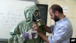Imágen de un video de un voluntario ajustando su traje contra gases neurotóxicos en Siria.