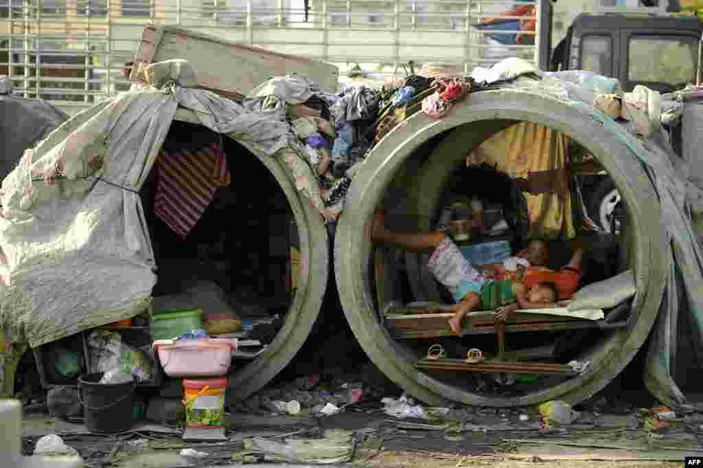 Families live in concrete pipes used as makeshift dwellings along a street in Manila, the Philippines.