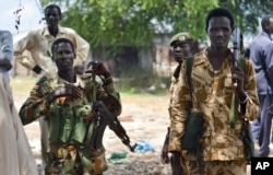 FILE - South Sudanese government soldiers patrol in Bentiu town, South Sudan, June 24, 2015.