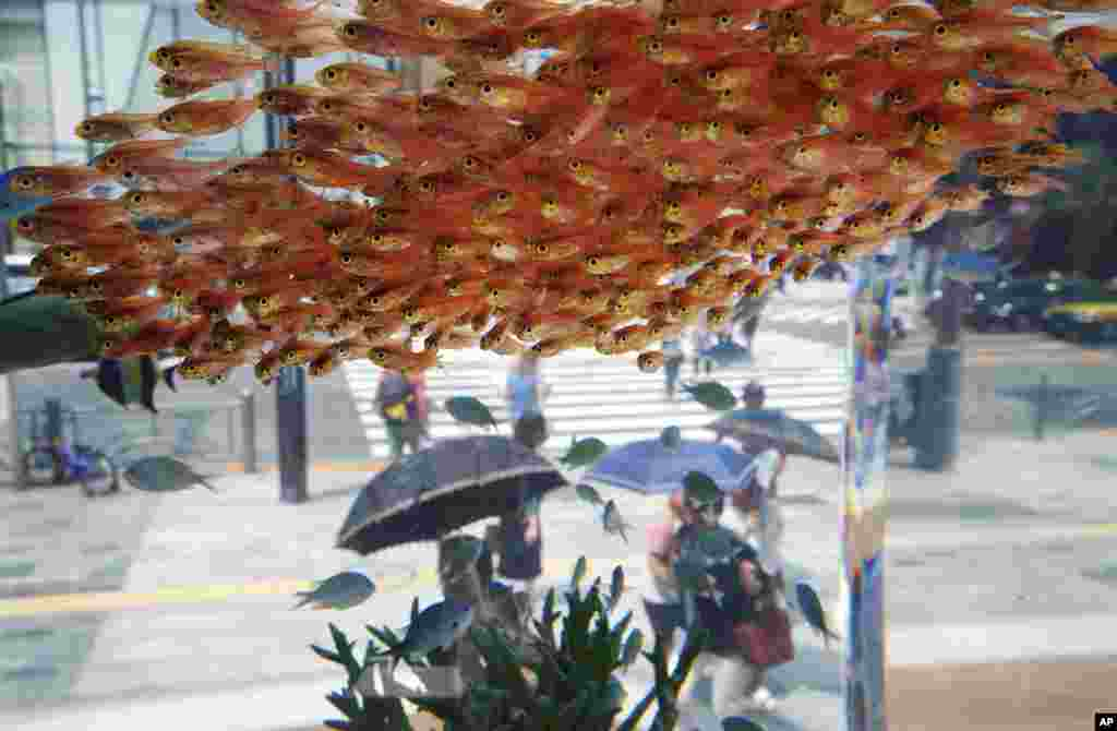 Passers-by look at fish swimming in a large glass tank displayed at Ginza shopping district in Tokyo, Japan.