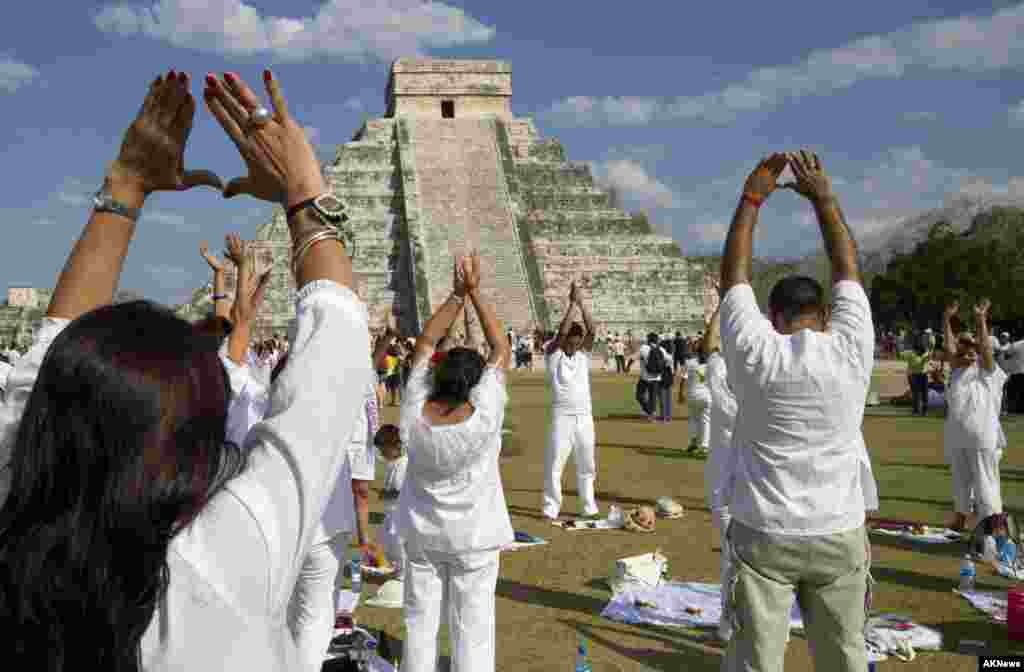 People raise their arms towards the sun while standing in front of the Kukulcan pyramid in Chichen Itza March 20, 2011.