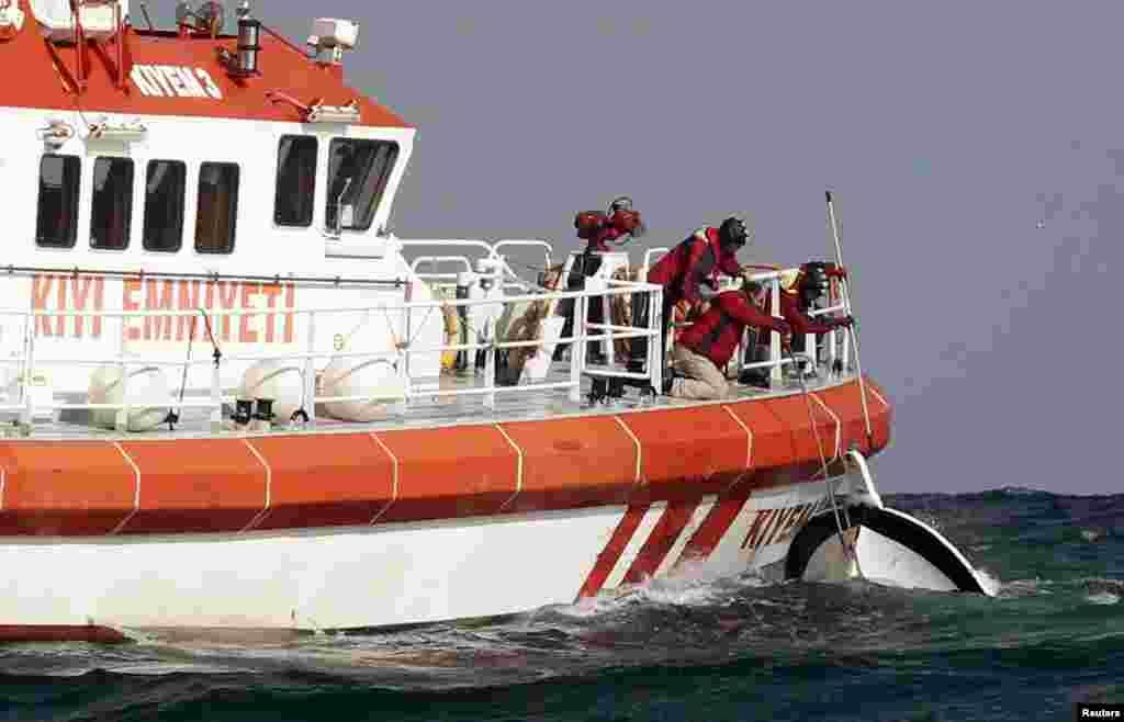 Rescuers retrieve a boat that sank off the Black Sea village of Garipce, near Istanbul, Turkey, Nov. 3, 2014.