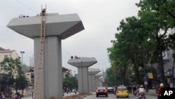 FILE - Motorists pass by a stretch of a metro railway project being constructed in Hanoi, Vietnam, April 7, 2013.