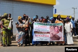 FILE - Women hold up a poster congratulating Jewel Howard Taylor, former wife of ex-President Charles Taylor, after she was re-elected senator in Monrovia, Jan. 3, 2015.