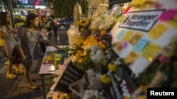 A woman places a flower at the Erawan shrine, the site of Monday's deadly blast, in central Bangkok, Thailand, Aug. 20, 2015.