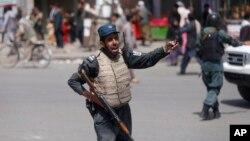 Un policier afghan s'active après un attentat à la voiture piégée près du siège de la police à Kaboul, en Afghanistan, le mercredi 7 août 2019.