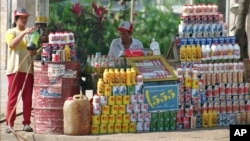 A vendor's wife fills up a two-littre bottle with gasoline for sale at a roadside stall in Phnom Penh, file photo.