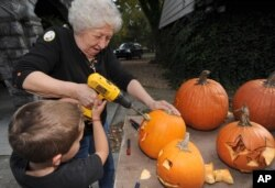 For Halloween, Betty Dillow of Bristol, Virgina helps her grandson carve his pumpkin with a power drill, 2013.