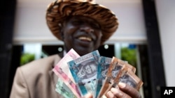 A South Sudanese man poses with a fistful of South Sudanese Pounds. A high-level minister says the government is planning to ban unofficial trading in U.S. dollars.