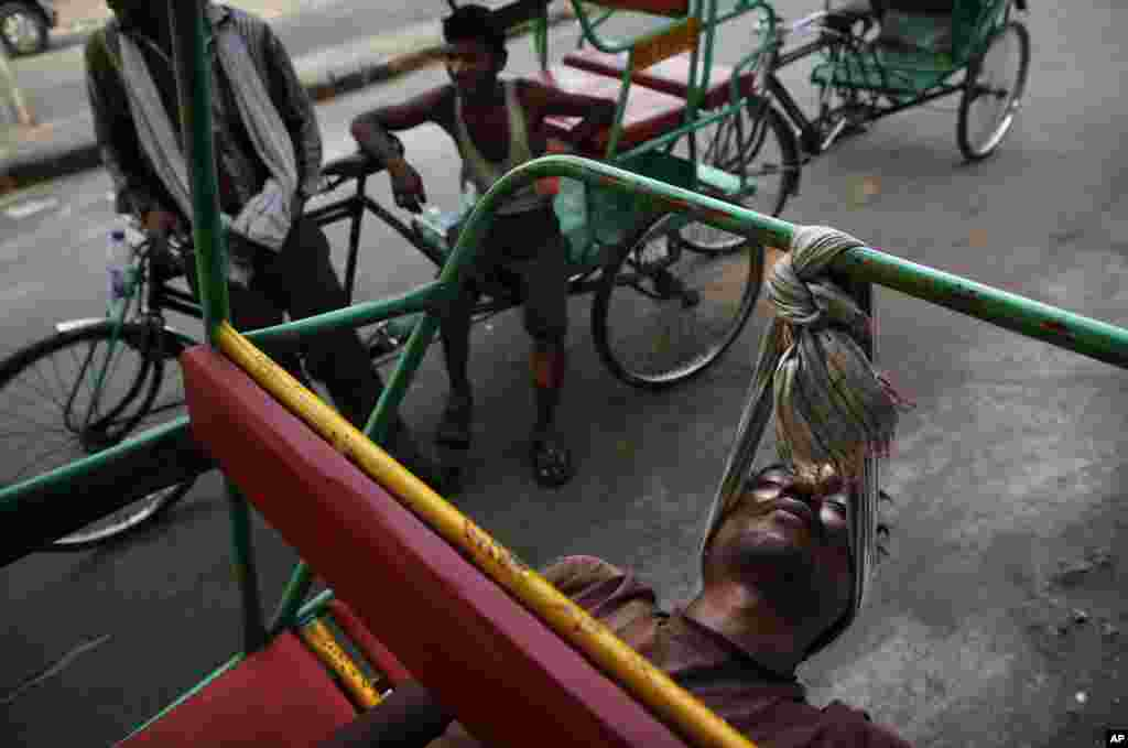 An Indian bicycle rickshaw walla uses a scarf to rest his head while sleeping on his rickshaw in New Delhi.