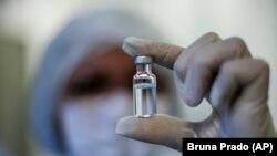 Seorang pekerja kesehatan menunjukkan botol vaksin AstraZeneca untuk COVID-19 yang diproduksi oleh Fiocruz Foundation di Rio de Janeiro, Brazil, Jumat, 12 Februari 2021. (Foto: AP/Bruna Prado)