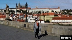 A woman wearing a face mask walks across the medieval Charles Bridge, as the Czech government shut sports, culture and social venues for two weeks to slow down the spread of the coronavirus disease (COVID-19), in Prague, Czech Republic, October 12.