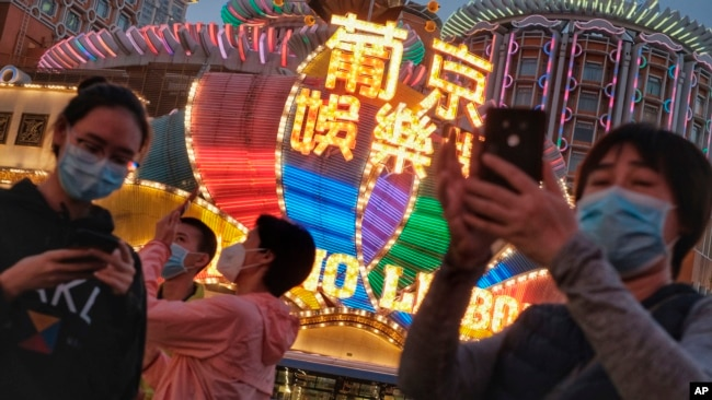 In this Jan, 23, 2020, photo released by Initium Media, tourists wearing masks, take photographs outside the Casino Lisboa in Macao, China. (Choi Chi Chio/Initium Media via AP)