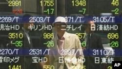 Seorang pria mengamati bergolaknya bursa saham di papan sekuritas di Tokyo (7/5). Saham-saham Asia turun hari Minggu seiring kekhawatiran krisis ekonomi di Eropa pasca pemilu Yunani dan Perancis.