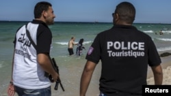FILE - Tourist police officers patrol at the beach in Sousse, Tunisia, July 1, 2015.