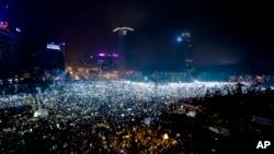ປະຊາຊົນຫຼາຍໝື່ນຄົນ ໄດ້ສ່ອງແສງໄຟ ອອກຈາກໂທລະ ສັບມືຖື ແລະທວນໄຟ ໃນລະຫວ່າງ ການປະທ້ວງ ຢູ່ຕໍ່ໜ້າ ຕຶກອາຄານລັດຖະບານ ໃນນະຄອນ Bucharest ຂອງ Romania, ວັນອາທິດ ທີ 5 ກຸມພາ 2017.