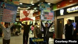 2013年4月8日黃文勳、張聖雨等人在廣州體育中心西地鐵站去天河城處舉牌抗議(博訊圖片/網友提供).