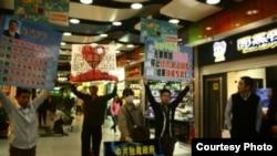 2013年4月8日黄文勋、张圣雨等人在广州体育中心西地铁站去天河城处举牌抗议(博讯图片/网友提供).