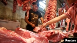 A customer chooses a cut of beef at a meat market in Beijing May 31, 2013. With more money in their pockets, millions of Chinese are switching to beef, driving imports to record levels and sending local meat firms abroad to scout for potential acquisition targets among beef farmers and processors.