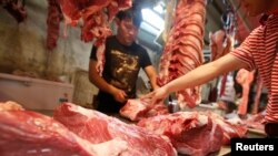 A customer chooses a cut of beef at a meat market in Beijing, May 2013. With more money in their pockets, millions of Chinese are seeking a richer diet and switching to beef. (FILE PHOTO)