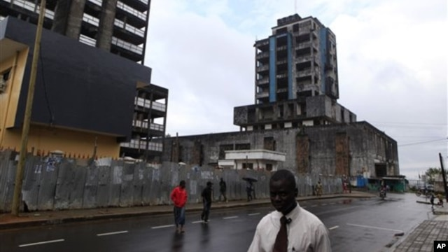 People walk past buildings damaged or unfinished as a result of Liberia's decade-and-a-half long civil war. In the post-war era, health officials are stepping up the fight against leprosy.