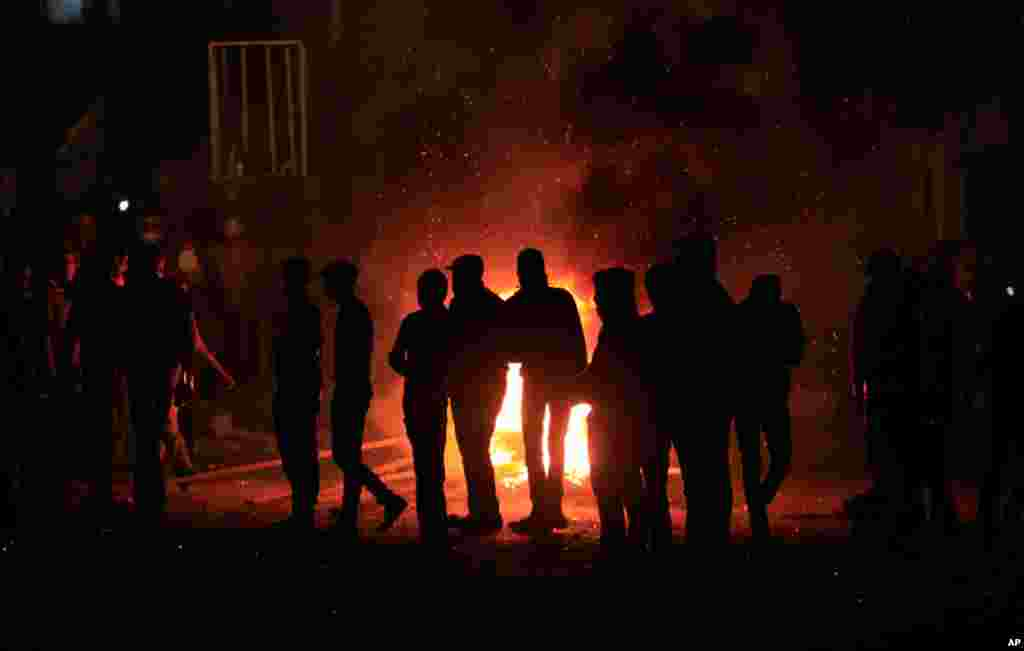Egyptian protesters gather around burning tires near a state security building in Port Said, Egypt, March 6, 2013.