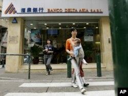 People walk near a branch of Banco Delta Asia in Macau, March 16, 2007.