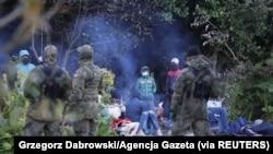 Petugas patroli perbatasan Polandia menjaga sekelompok migran yang berusaha melintasi perbatasan antara Belarus dan Polandia di dekat desa Usnarz Gorny, Polandia, 18 Agustus 2021. (Foto: Grzegorz Dabrowski/Agencja Gazeta via REUTERS)