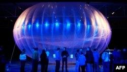 FILE - Visitors stand next to a high altitude WiFi internet hub, a Google Project Loon balloon, on display at the Air Force Museum in Christchurch.